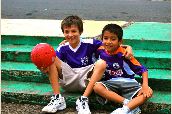 Play soccer with local children