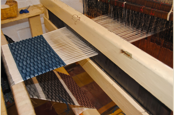 Naturally dyed indigo thread on a foot loom in Olga's workshop.