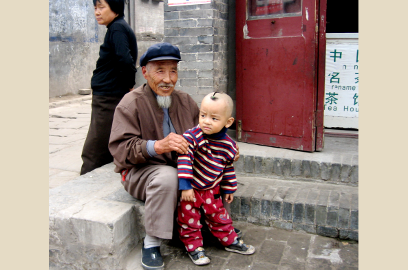 Proud grandfather in the Hutong area of Beijing