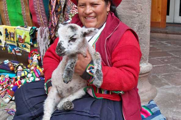 Peruvian woman poses with a furry friend in Cusco